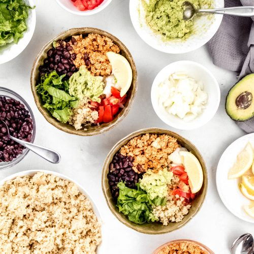 mexican quinoa bowl with tofu sofritas, black beans, onions, tomatoes, lettuce, and guacamole.